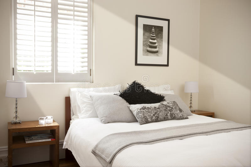Bedroom Bed Interior Light. A bedroom with window light coming through the shutters. With pillows and bedside tables