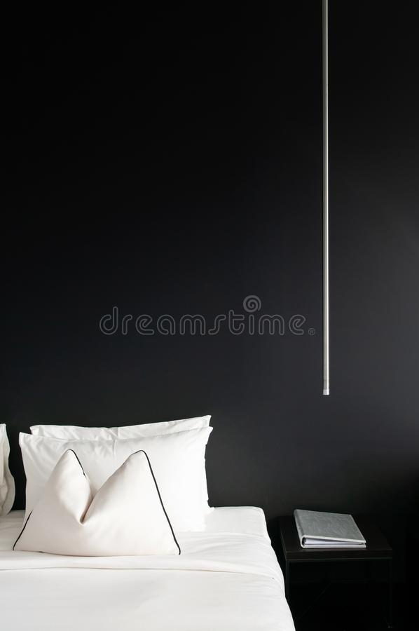 Bedroom with black wall white bed, pillows modern side table, la stock photos