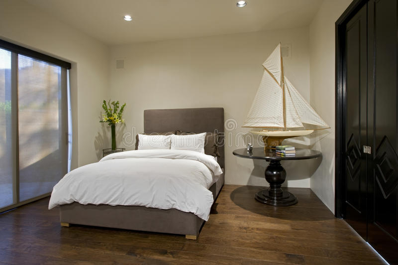 Bedroom With Boat Model On Side Table. Interior of contemporary bedroom with boat model on side table stock images