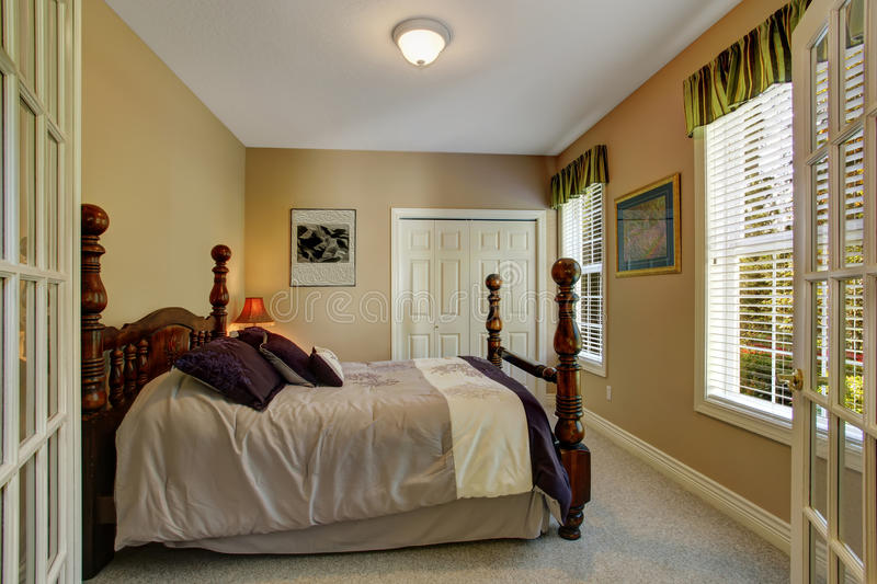 Bedroom with carved wood bed. Beige bedroom with closet and carved wood bed with high poles royalty free stock photo
