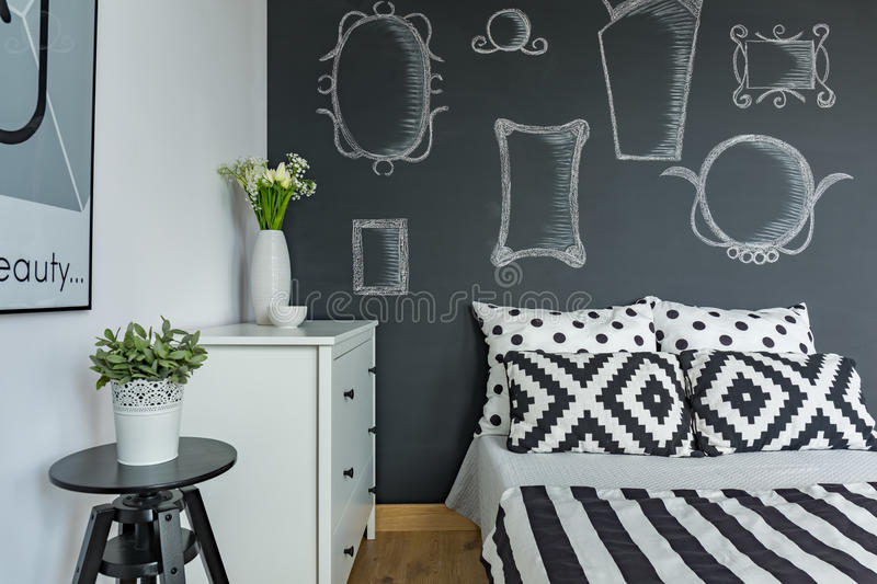 Bedroom with chalkboard wall. Modern bedroom with chalkboard wall and double bed royalty free stock images