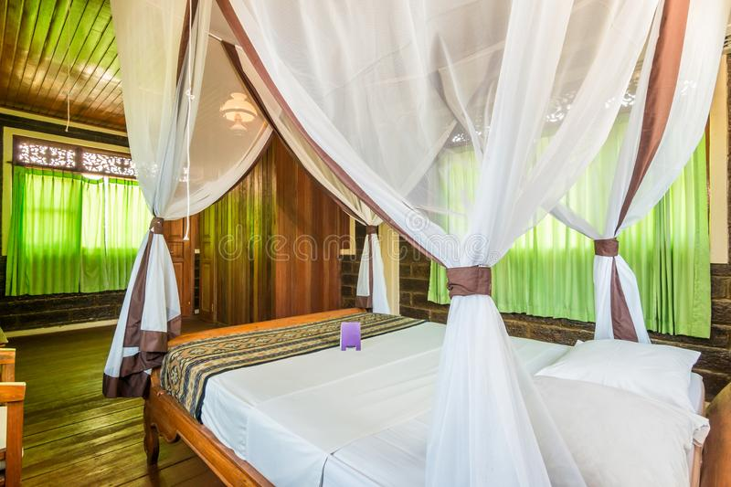 Super Deluxe Traditional Villa Bedroom. Bedroom at cheap prices traditional villa in Bali. Photographed during day time. The wall painted with dark color. The royalty free stock images