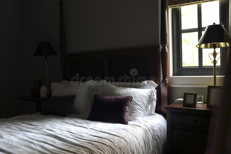 The bedroom with comparative and intense light and shade. A single light source illuminate, bed part of the bright part of the dark stock photography