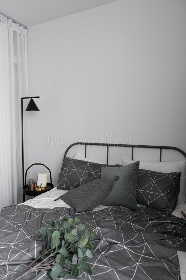 Bedroom corner in scandinavian style with gray metal bed and black side table with minimal floor lamp stock photo