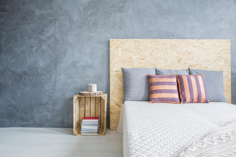Bedroom with diy, wood bed. Grey bedroom with diy, wood bed and crate side table royalty free stock photography