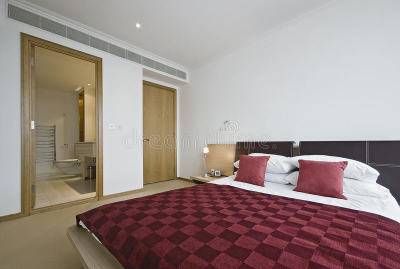 Bedroom with en-suite. Luxury modern bedroom detail with en-suite bathroom royalty free stock images