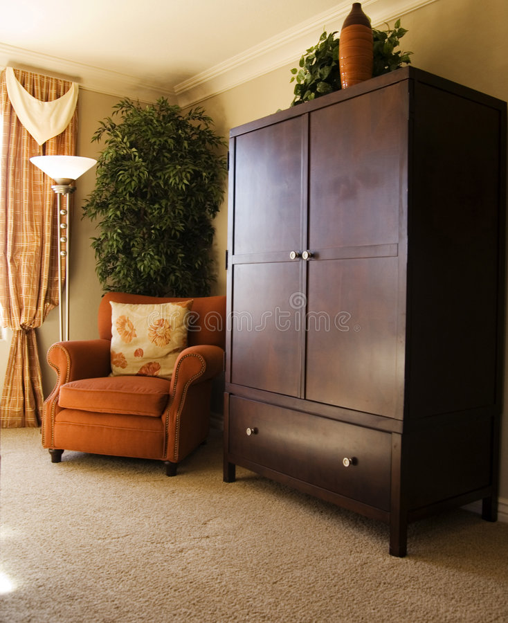 Bedroom furniture. Elegant bedroom wooden furniture chest and entertainment area with comfy chair royalty free stock photo