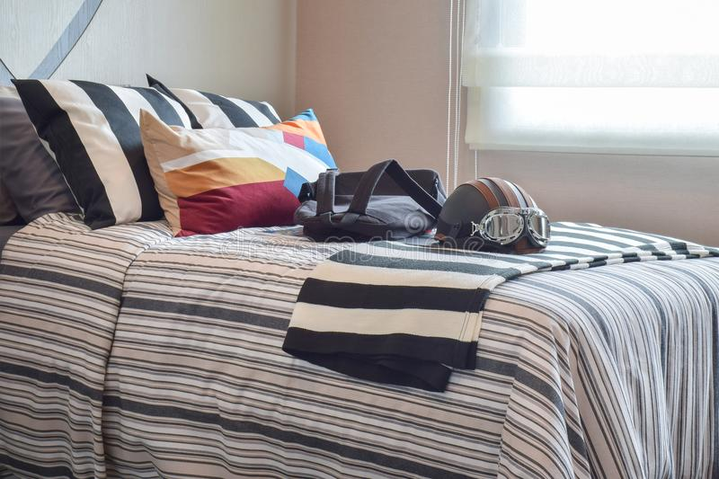 Bedroom with helmet and bag on striped bedding. Modern bedroom with helmet and bag on striped bedding stock images