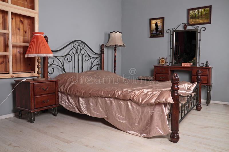 Bedroom interior. Bedroom with gray to walls, a double iron bed, a bedside table of a pier glass and night lamps royalty free stock photo