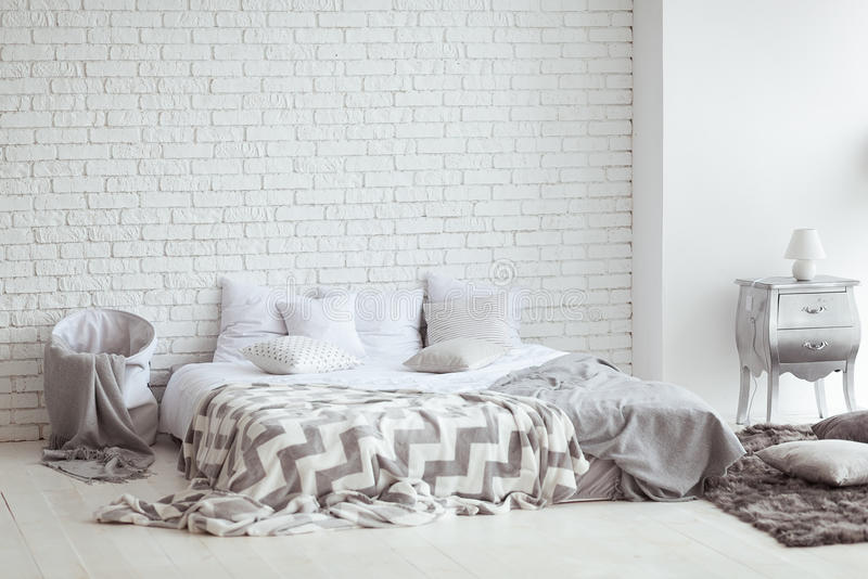 Bedroom interior with a brick wall with a bed and bedside tables royalty free stock image