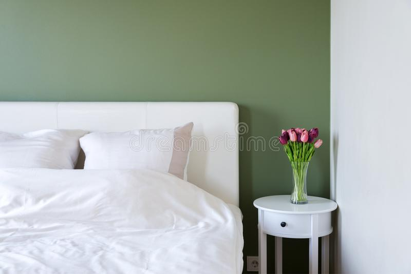 Bedroom interior with white bed and bedside table with flowers stock images