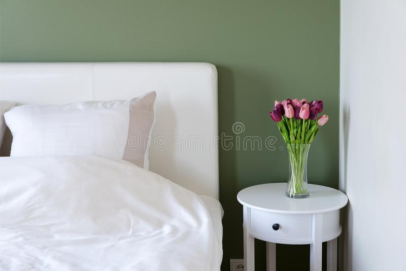 Bedroom interior with white bed and bedside table with flowers stock photography