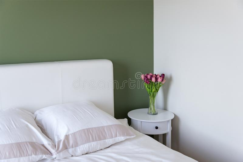 Bedroom interior with white bed and bedside table with flowers royalty free stock image