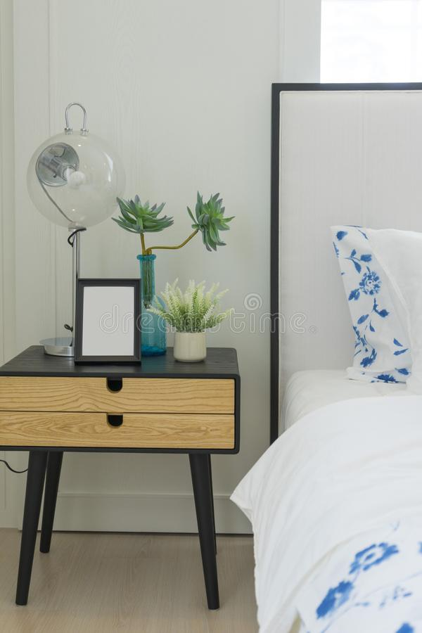Free Bedroom Interior With Striped Pillow On Bed And Bedside Table Lamp With Picture Frame On It. Royalty Free Stock Image - 161096756