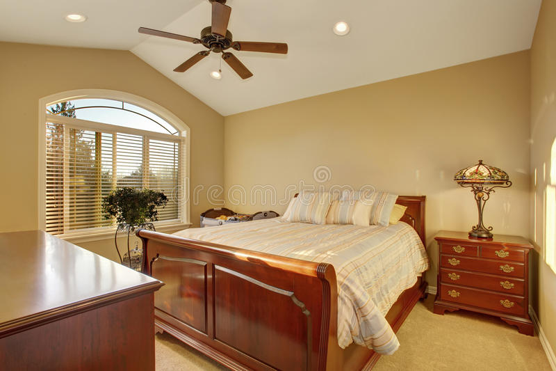 Bedroom interior withh antique wooden furniture and beige walls. Bedroom interior withh antique wooden furniture, big bed and beige walls stock photo