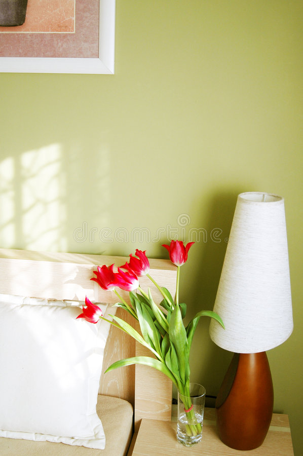 Bedroom lamp. A bedside lamp and red flowers standing near the bed, morning light coming from the window stock photos