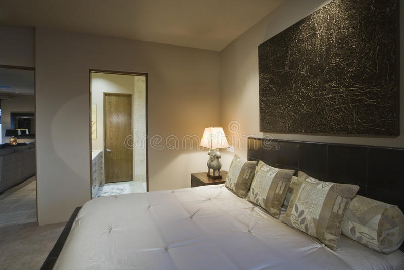 Bedroom With Lit Bedside Lamp stock image