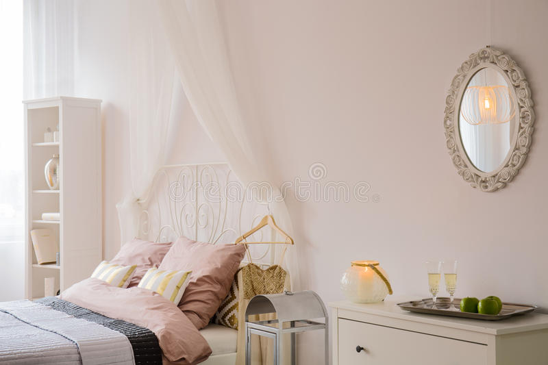 Bedroom with mirror and dresser. Light bedroom with bed, mirror, dresser and bookcase royalty free stock images