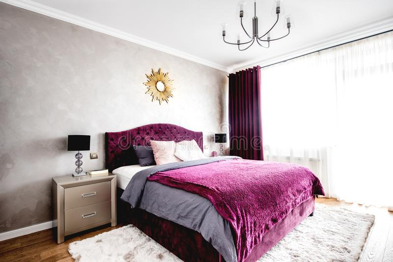 Bedroom with modern furniture design, double bed and warm colors. Spacious bedroom with modern furniture design, double bed and warm colors royalty free stock photography