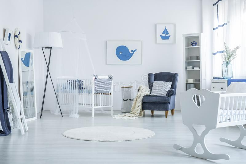 Bedroom for newborn. Bedroom prepared for a newborn with wooden cradle, nautical posters and white crib royalty free stock photography