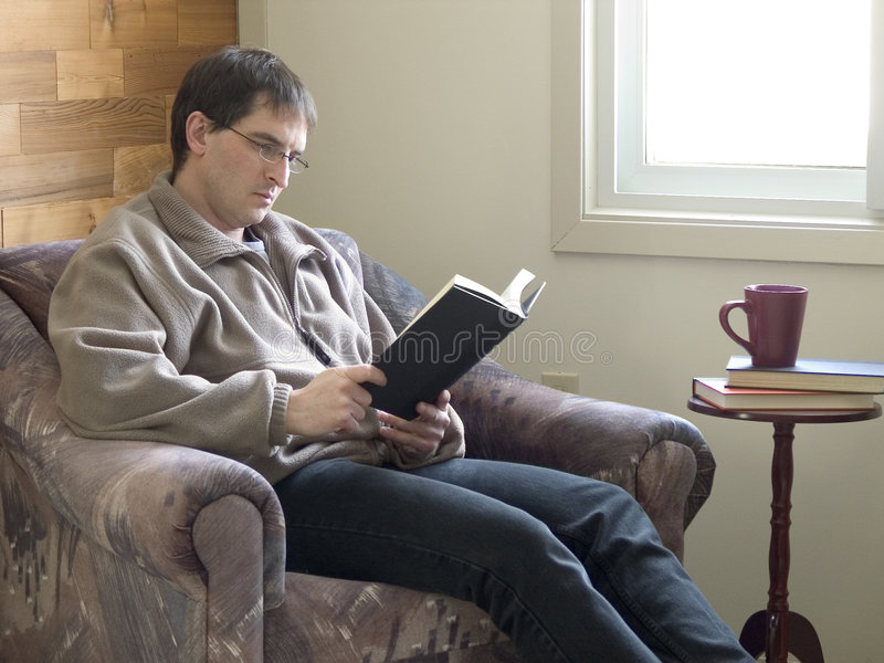 Bedroom Reader. Man sitting by a window, reading a book