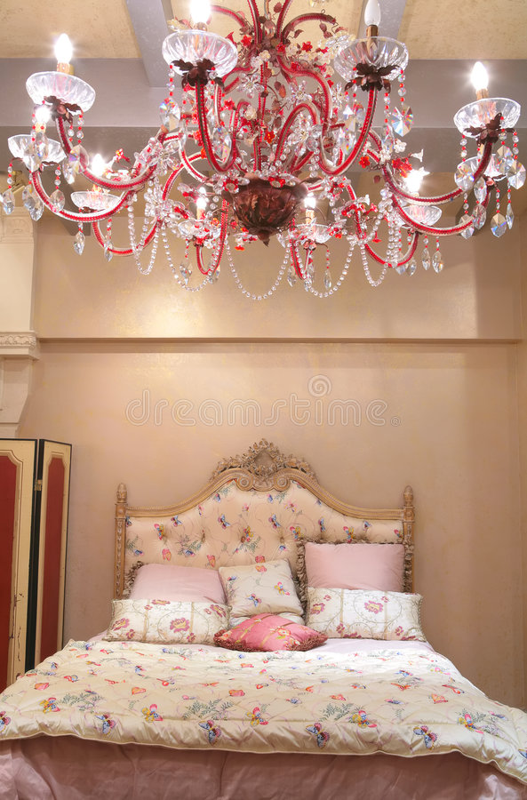 Bedroom with red chandelier. Interior of luxurious bedroom with red chandelier from crystal royalty free stock photo