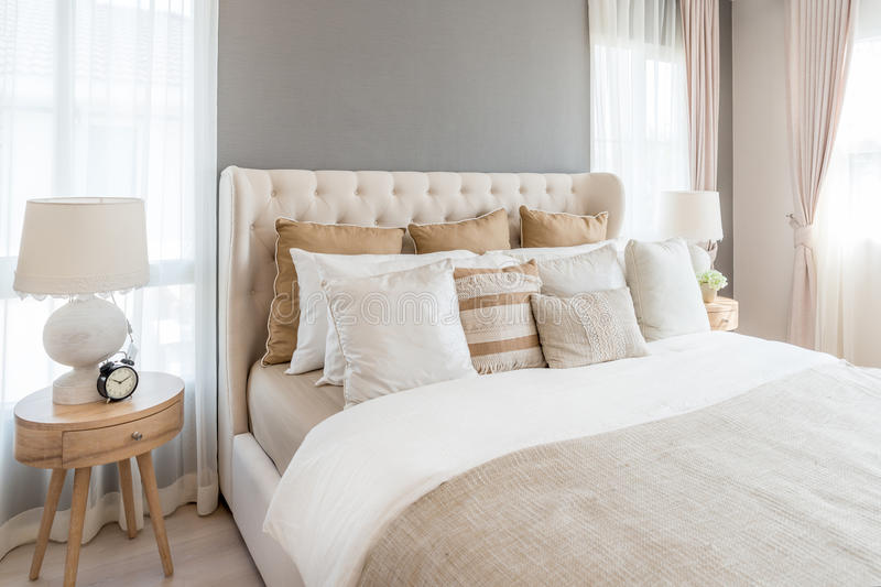 Bedroom in soft light colors. big comfortable double bed in elegant classic bedroom at home. royalty free stock photography