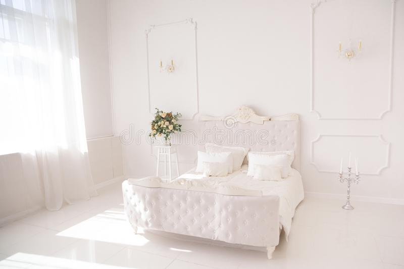 Bedroom in soft light colors. big comfortable double bed in elegant classic bedroom.  stock image