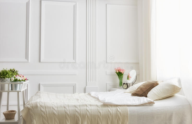 Bedroom in soft light colors. Big comfortable double bed in elegant classic bedroom royalty free stock images