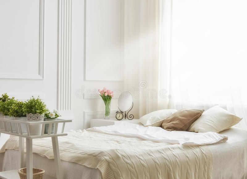 Bedroom in soft light colors. Big comfortable double bed in elegant classic bedroom royalty free stock image