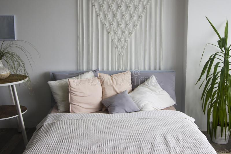 Bedroom in soft light colors. big comfortable double bed in elegant classic bedroom. White double bed with pillows. Bedroom interi stock photography