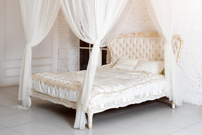 Bedroom in soft light colors. Big comfortable four poster double bed in elegant classic bedroom. Luxury elegant white with gold in stock image