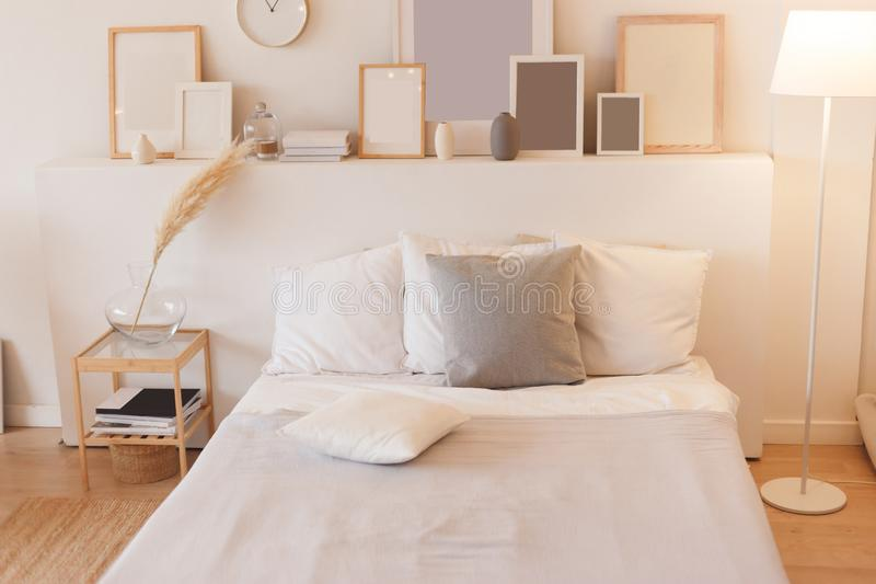Bedroom with switched on floor lamp and photo frames stock photography