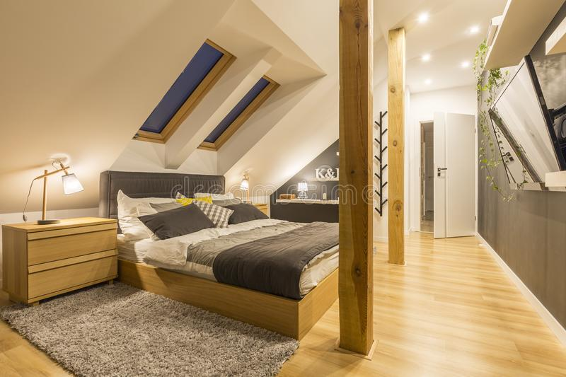 Bedroom with tv. Spacious bedroom with king-size bed, wooden accessories and tv stock photography