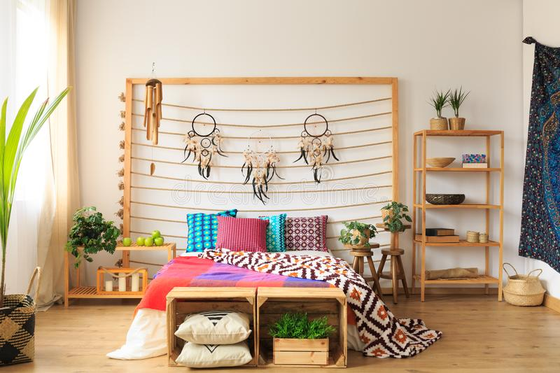 Bedroom with wooden furniture. Ethnic spacious colorful bedroom with wooden furniture stock photos