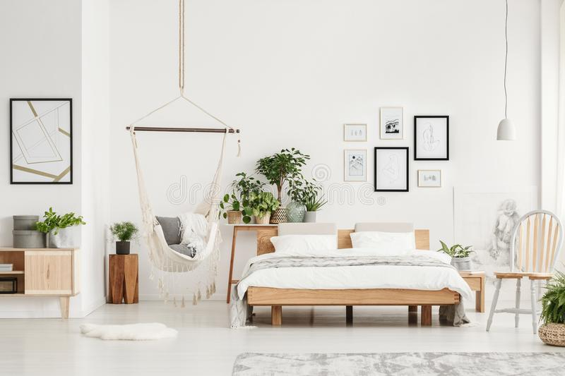 Bedroom with wooden furniture. Spacious bedroom interior with wooden furniture such as a bed, chair and cupboard stock photography