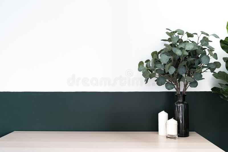 Bedroom working corner and wooden table decorated with white candle in glass and artificial plant in a black glass vase on green royalty free stock photography