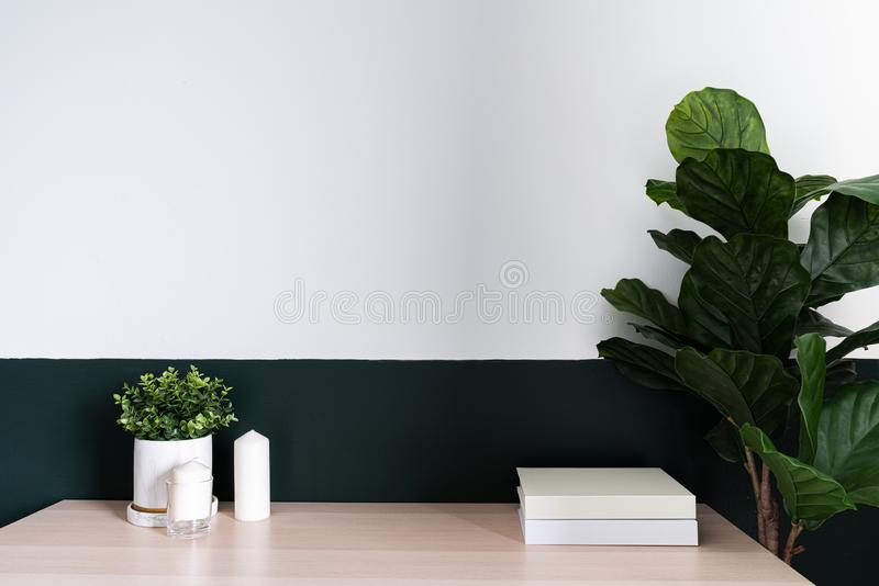 Bedroom working corner and wooden table decorated with white candle in glass and artificial plant in a marble pattern vase on stock images