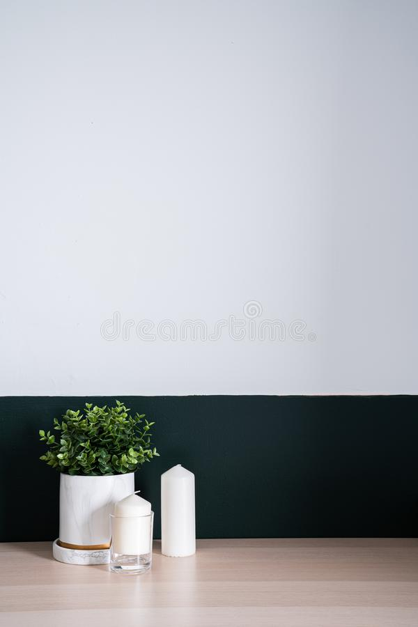 Bedroom working corner and wooden table decorated with white candle in glass and artificial plant in a marble pattern vase on stock image