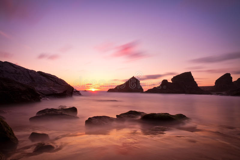 Bedruthan Steps at sunset with violet skies, Cornw. All, England, UK royalty free stock images
