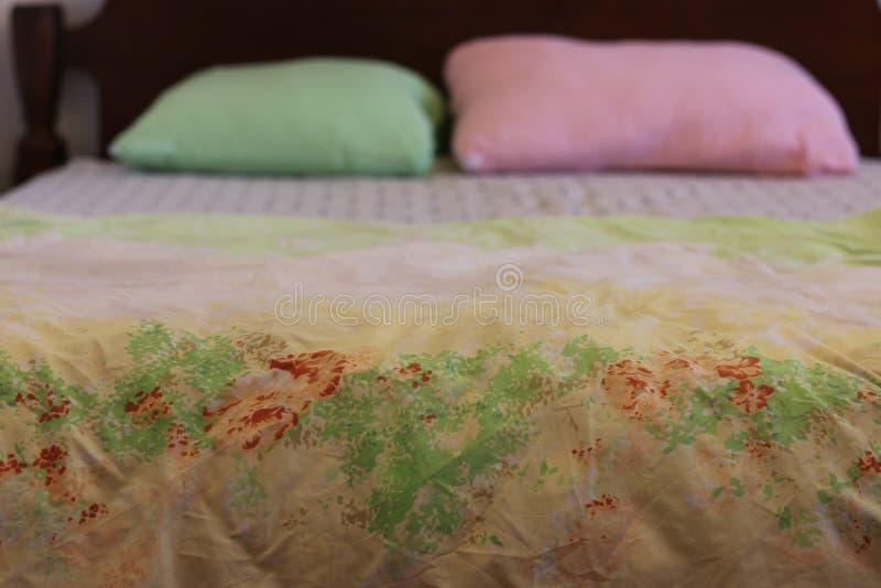 Bedsheets con las almohadas rosadas y verdes fotografía de archivo libre de regalías