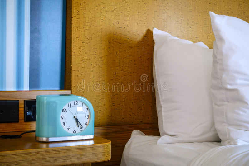 Bedside table. Fragment of a bed and a bedside table with alarm clock at a hotel stock photos