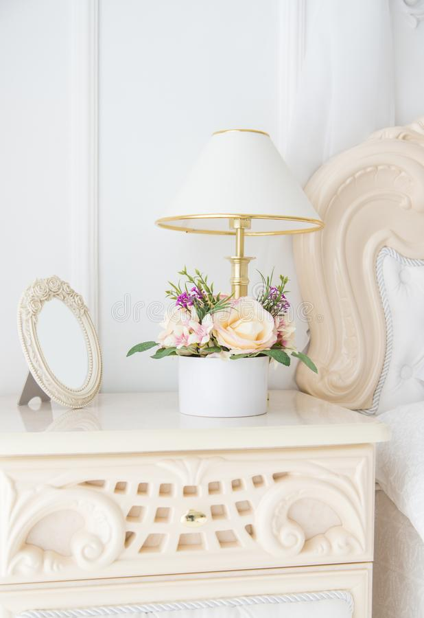 Bedside table with lamp and empty photograph frame. In white bedroom royalty free stock images