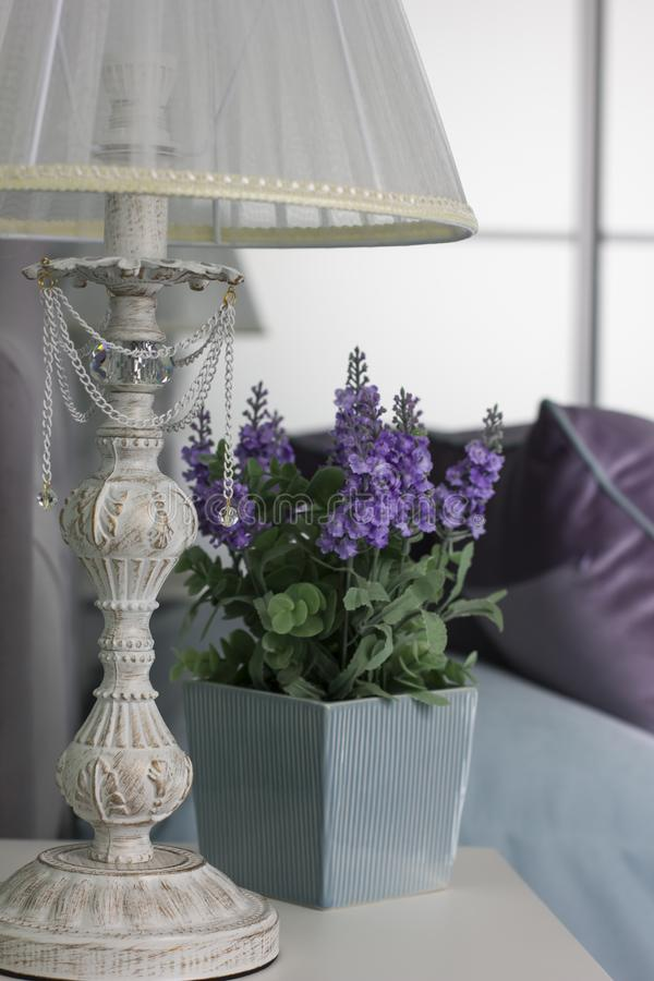 Bedside table, lamp, pot with flower, interior in Provence style. The Bedside table, lamp, pot with flower, interior in Provence style royalty free stock photography