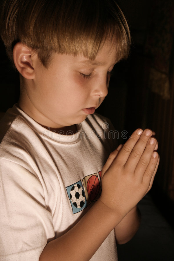 Bedtime prayer. Kneeling boy with palms together in prayer stock photography