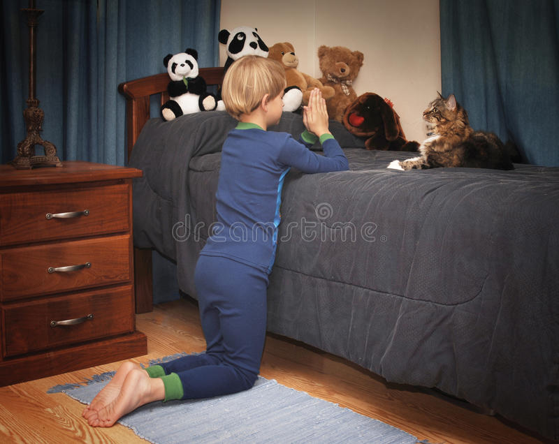 Bedtime Prayers. Boy kneeling at bedside saying prayers in pajamas royalty free stock photos