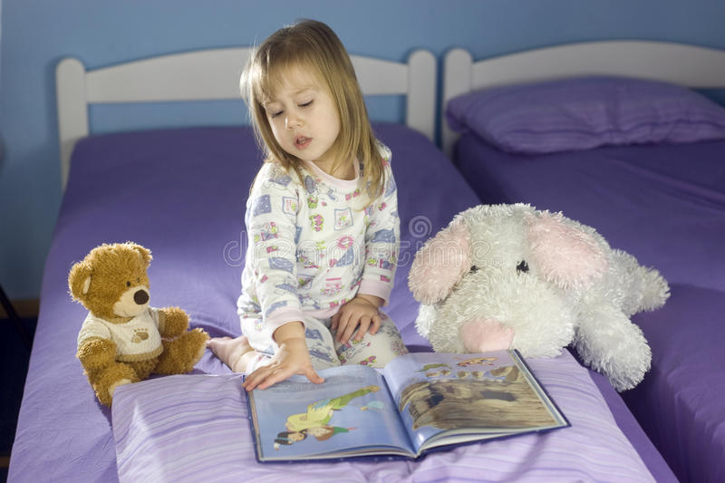 Bedtime story. Little girl with teddy bear looking at her favorite book before bedtime royalty free stock photo