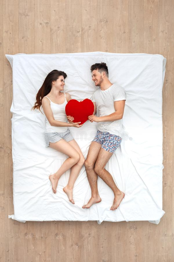 Bedtime. Young couple lying on bed top view holding heart shape pillow looking at each other smiling cheerful stock image