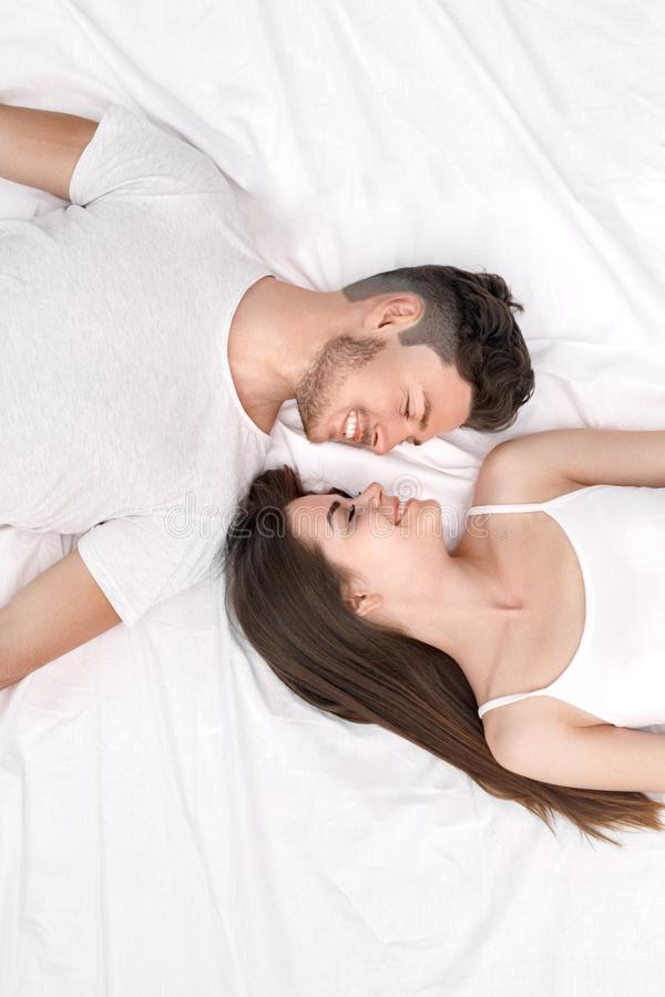 Bedtime. Young couple lying on bed top view isolated on white looking at each other joyful stock images