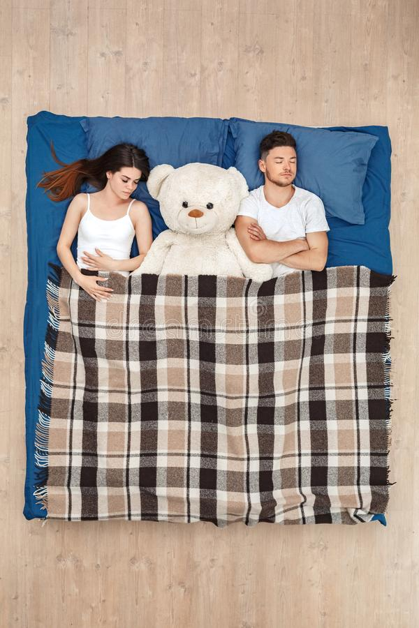 Bedtime. Young couple sleeping on bed top view under blanket with teddy peaceful royalty free stock photo